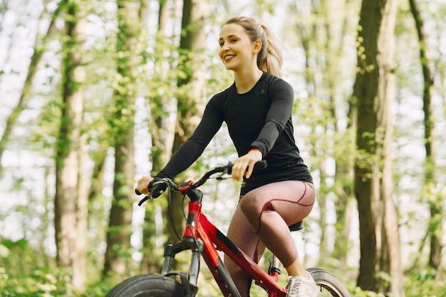 Frau, die ein mountainbike im wald reitet Kostenlose Fotos