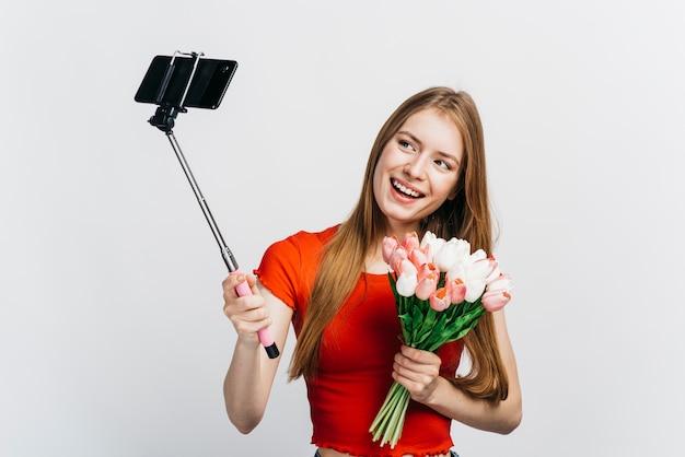 Frau, die ein selfie beim halten eines blumenstraußes der tulpen nimmt Kostenlose Fotos