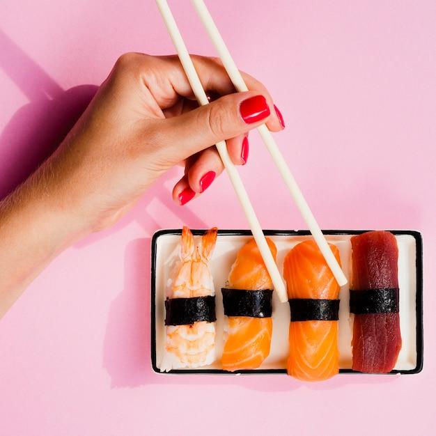 Frau, die ein sushi von der platte wählt Kostenlose Fotos