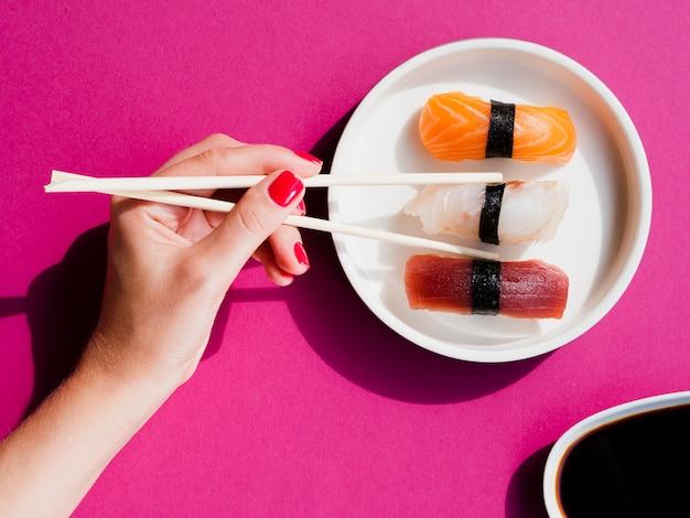 Frau, die ein sushistück mit essstäbchen nimmt Kostenlose Fotos