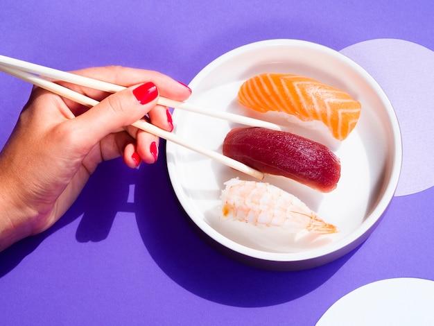 Frau, die ein thunfischsushi von einer weißen schüssel mit sushi nimmt Kostenlose Fotos