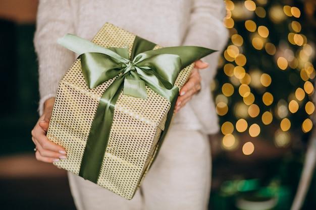 Frau, die ein weihnachtsgeschenk, kastenabschluß hochhält Kostenlose Fotos