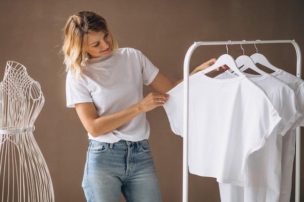 Frau, die ein weißes hemd wählt Kostenlose Fotos