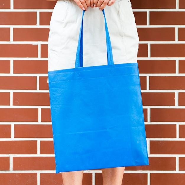 Frau, die eine blaue tasche hält Kostenlose Fotos