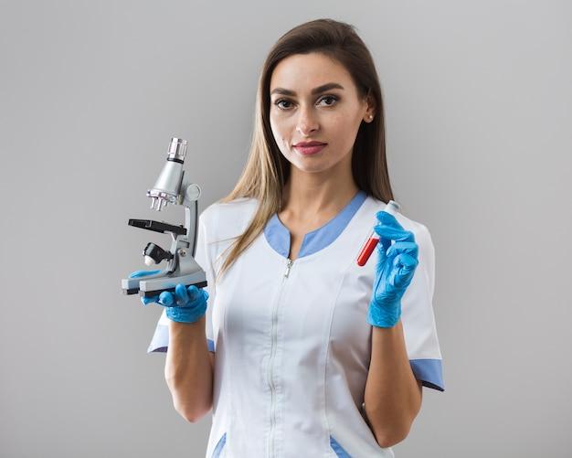 Frau, die eine blutprobe und ein mikroskop hält Kostenlose Fotos