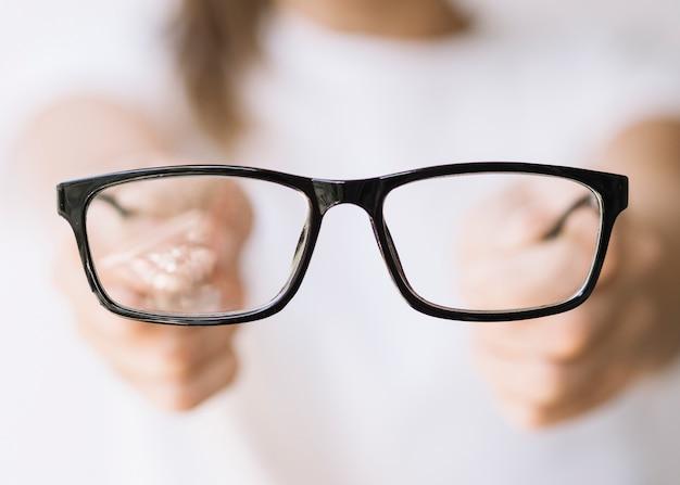 Frau, die eine brille mit schwarzem rahmen hält Kostenlose Fotos