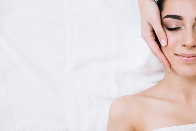 Frau, die eine entspannende gesichtsmassage empfängt Kostenlose Fotos