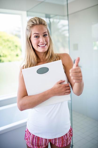Frau, die eine gewichtungsskala mit den daumen oben im badezimmer hält Premium Fotos