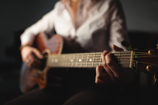 Frau, die eine gitarre in der musikschule spielt Kostenlose Fotos