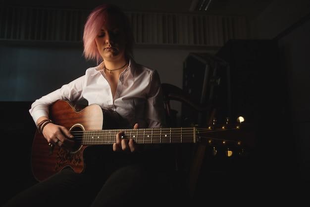 Frau, die eine gitarre spielt Kostenlose Fotos