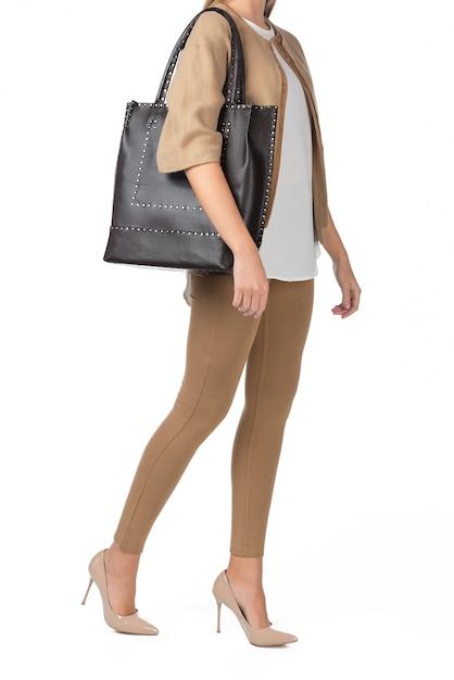 Frau, die eine handtasche getrennt auf weiß anhält Premium Fotos