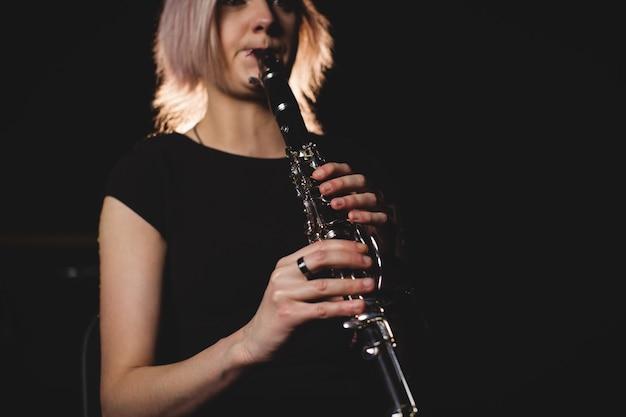 Frau, die eine klarinette in der musikschule spielt Kostenlose Fotos