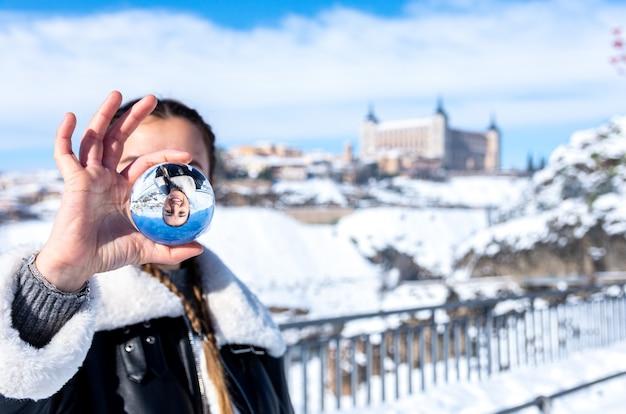 Frau, die eine kristallkugel in der verschneiten stadt toledo hält Premium Fotos