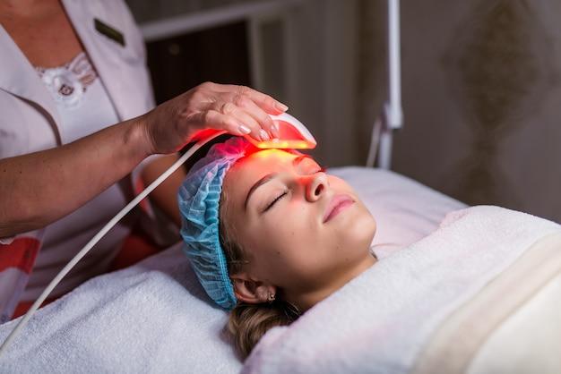 Frau, die eine laser-hautbehandlung in einer hautpflegeklinik hat Premium Fotos