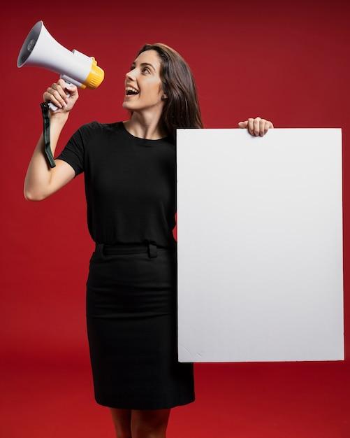 Frau, die eine leere fahne beim schreien in einem megaphon hält Premium Fotos