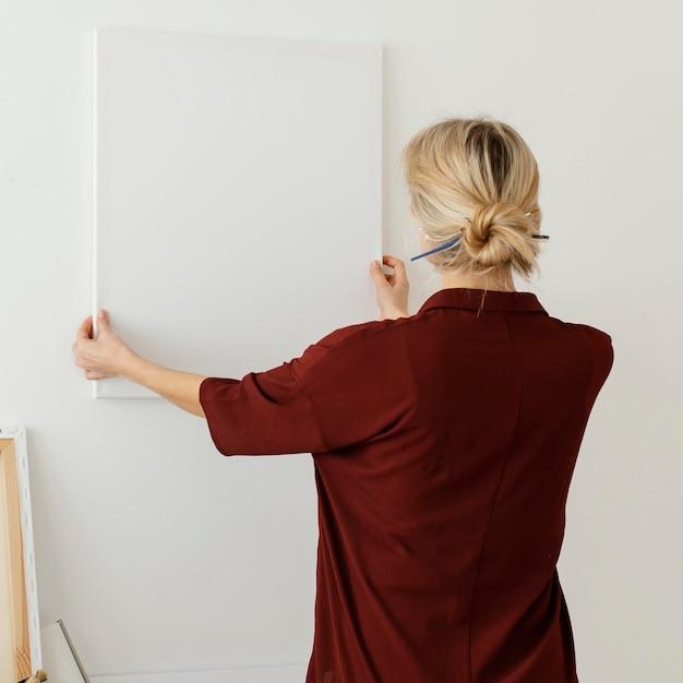 Frau, die eine leere leinwand hält Kostenlose Fotos