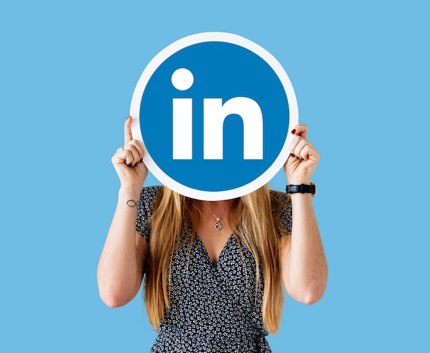 Frau, die eine linkedin-ikone anhält Premium Fotos