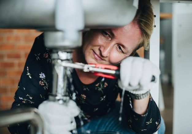 Frau, die eine spülbecken repariert Premium Fotos