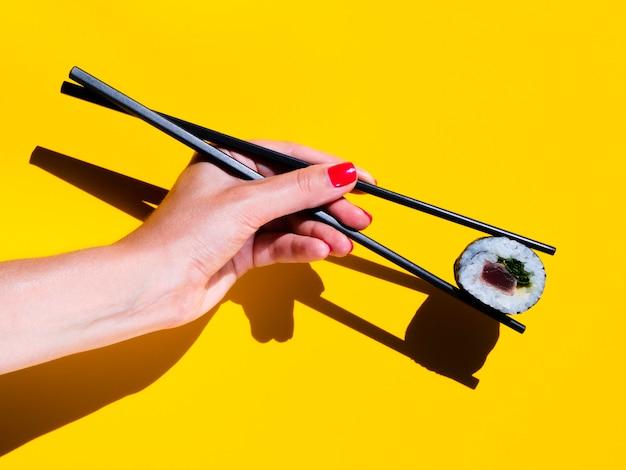 Frau, die eine sushirolle auf einem gelben hintergrund hält Kostenlose Fotos
