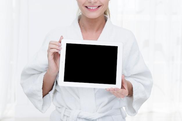 Frau, die eine tablette in einem badekurort verwendet Kostenlose Fotos