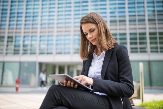 Frau, die eine tablette vor ihrem büro verwendet Premium Fotos