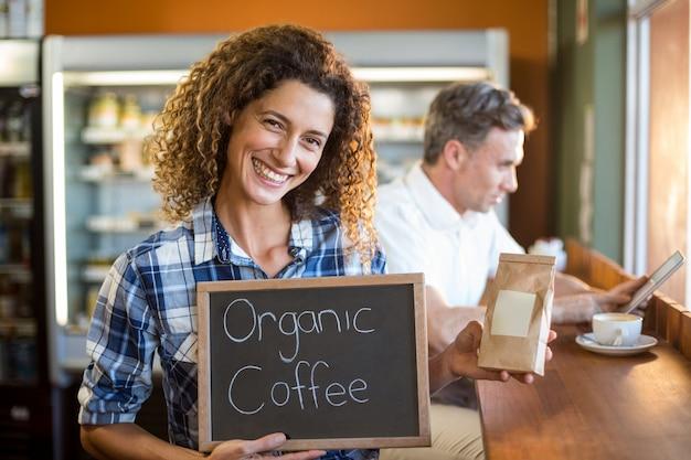 Frau, die eine tafel hält, die bio-kaffee liest Premium Fotos
