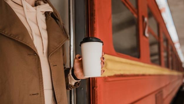 Frau, die eine tasse kaffee neben zug hält Kostenlose Fotos