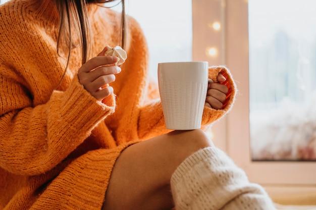 Frau, die eine tasse tee drinnen hält Kostenlose Fotos