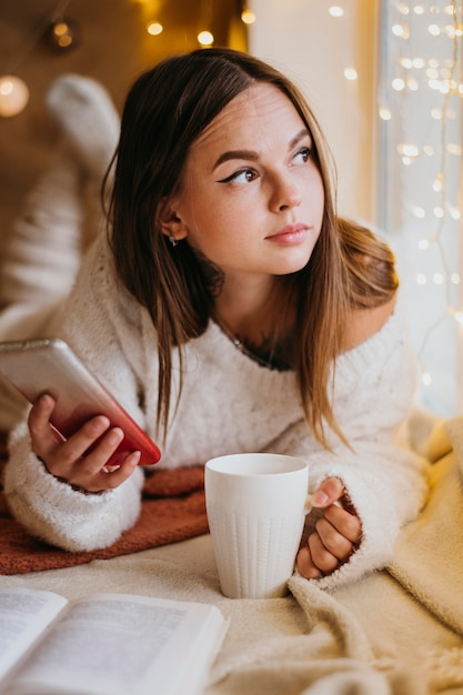 Frau, die eine tasse tee hält, während sie wegschaut Kostenlose Fotos