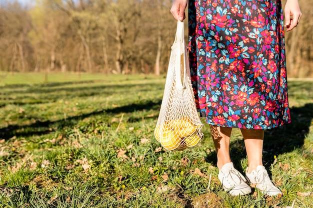 Frau, die eine tüte obst im park hält Kostenlose Fotos
