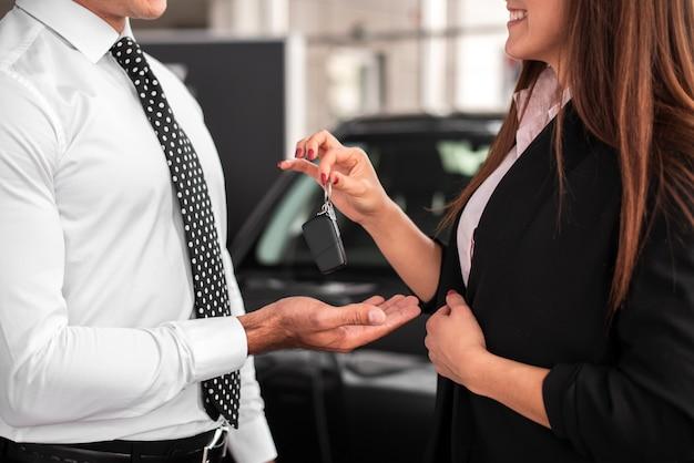 Frau, die einem mann autoschlüssel übergibt Premium Fotos