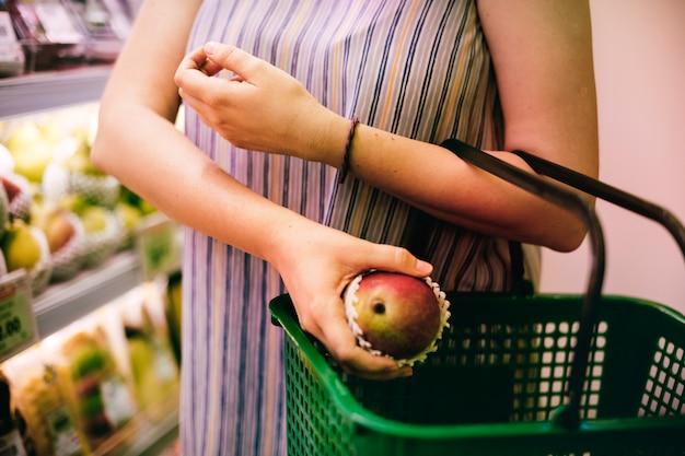 Frau, die einen apfel am supermarkt vorwählt Kostenlose Fotos