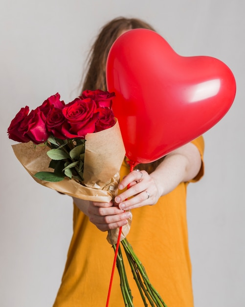 Frau, die einen blumenstrauß von rosen und von ballon anbietet Kostenlose Fotos