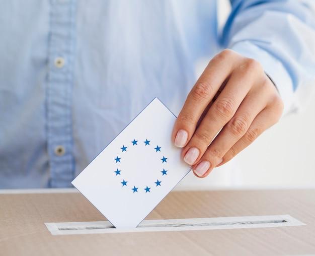 Frau, die einen europäischen stimmzettel in kasten einsetzt Kostenlose Fotos