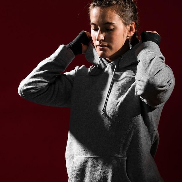 Frau, die einen hoodie trägt und ihre augen schließen lässt Kostenlose Fotos