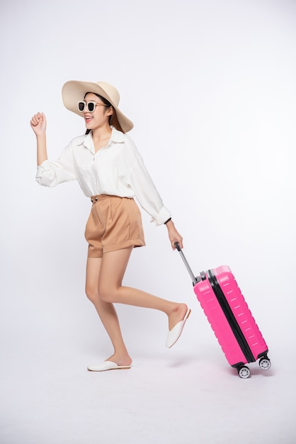 Frau, die einen hut, eine brille und die griffe der koffer trägt, um zu reisen Kostenlose Fotos