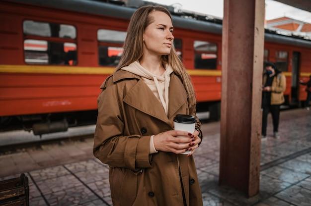 Frau, die einen kaffee im bahnhof hält Kostenlose Fotos