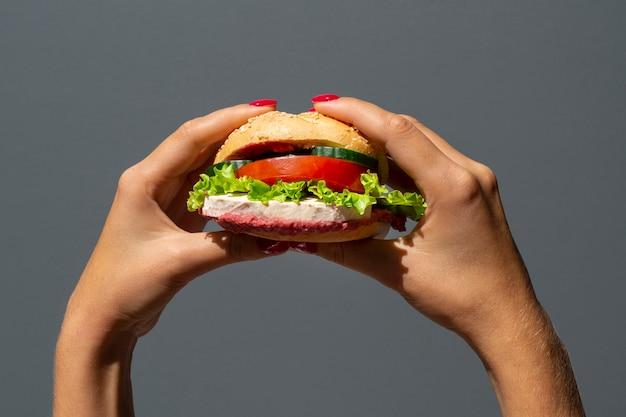 Frau, die einen köstlichen veggieburger hält Kostenlose Fotos