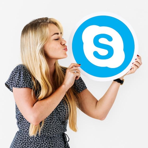 Frau, die einen kuss zu einer skype-ikone durchbrennt Kostenlose Fotos