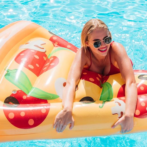 Frau, die einen pizzaschwimmenfloss hält Kostenlose Fotos