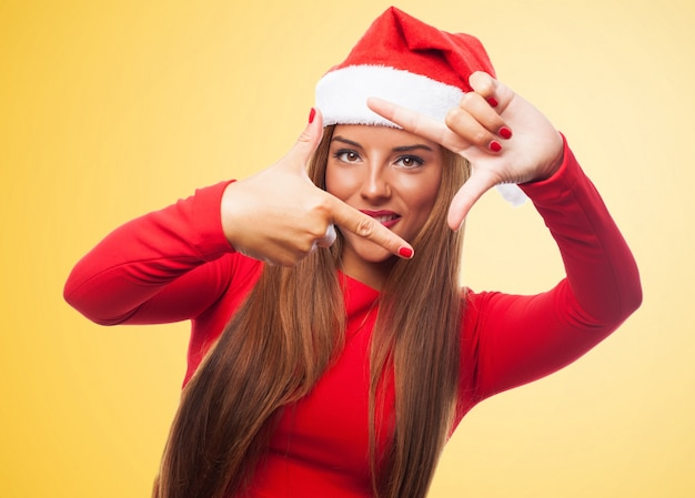 Frau, die einen rahmen mit den fingern in einem gelben hintergrund Kostenlose Fotos