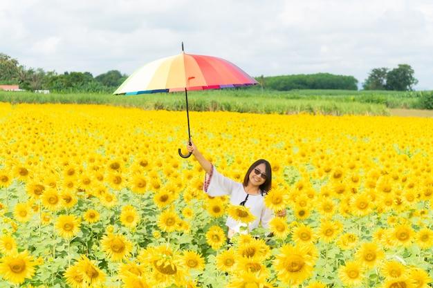Frau, die einen regenschirm auf einem sonnenblumengebiet hält. Premium Fotos