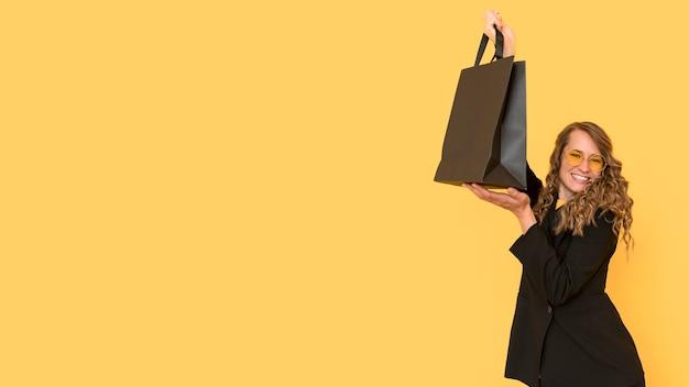 Frau, die einen schwarzen einkaufstaschenkopierraum hält Kostenlose Fotos