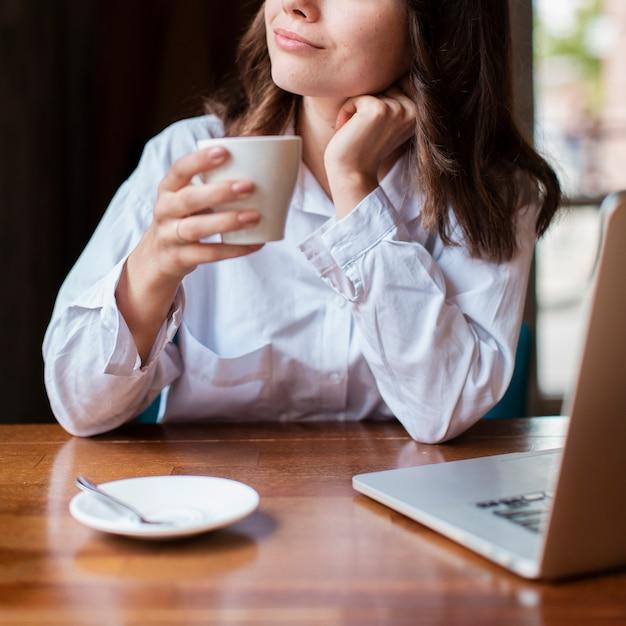 Frau, die einen tasse kaffee mit laptop auf schreibtisch hält Kostenlose Fotos