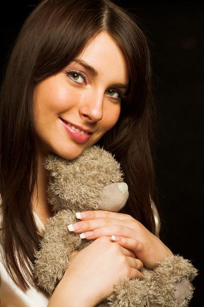 Frau, die einen teddybären hält Premium Fotos