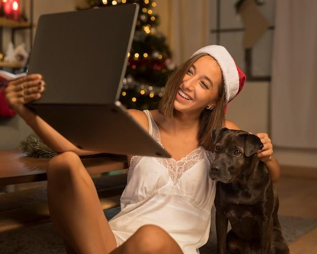 Frau, die einen videoanruf an weihnachten mit ihrem hund und der weihnachtsmütze hat Kostenlose Fotos
