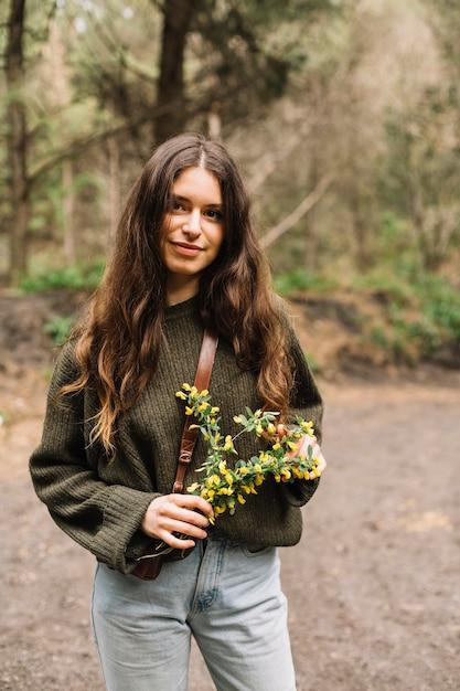 Frau, die einige wildflowers in der natur hält Kostenlose Fotos