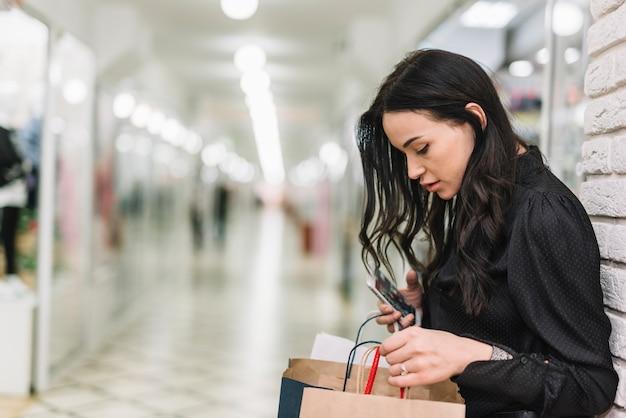 Frau, die einkaufstaschen im speicher überprüft Kostenlose Fotos
