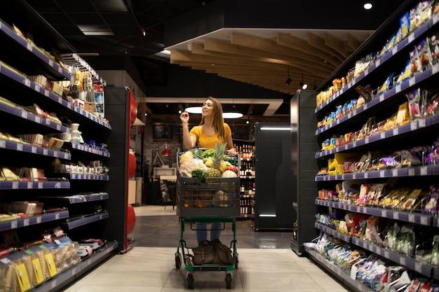 Frau, die einkaufswagen zwischen regalen im supermarkt schiebt Kostenlose Fotos