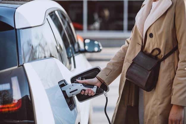 Frau, die elektroauto an der elektrischen tankstelle auflädt Kostenlose Fotos